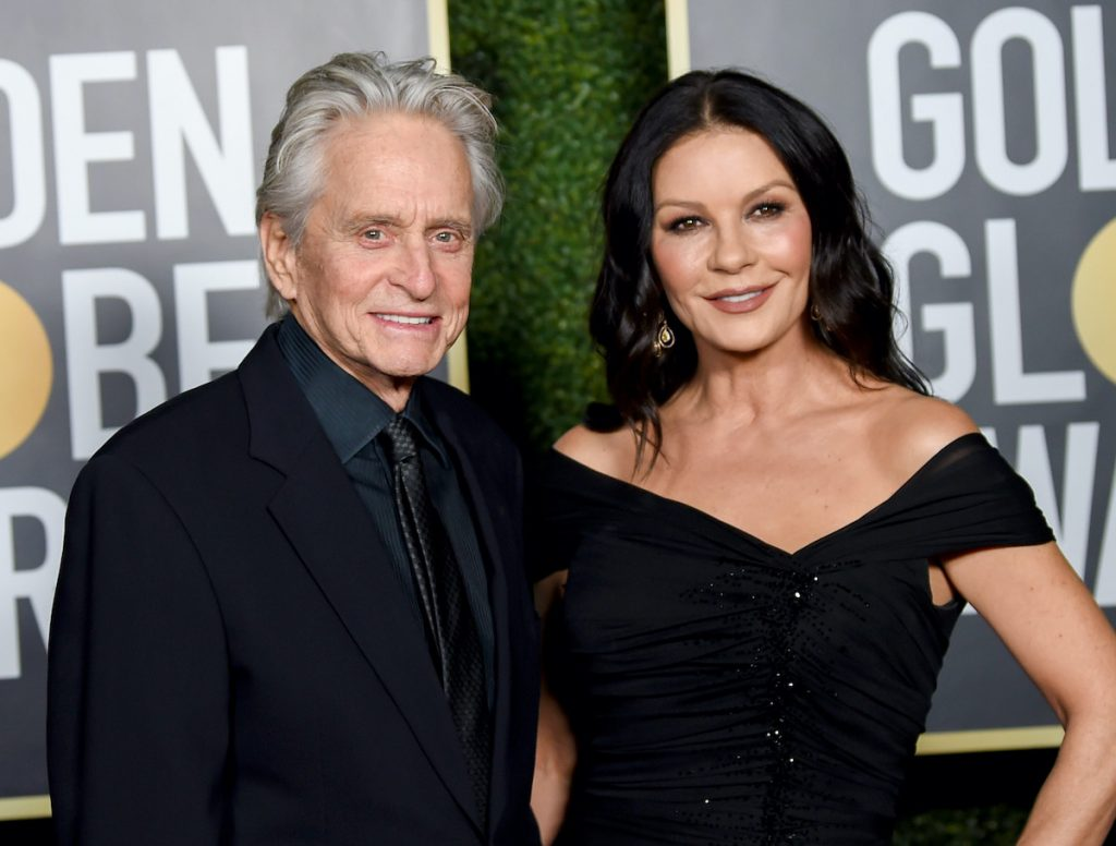 Michael Douglas in a black suit and Catherine Zeta-Jones in a black gown while smiling on the red carpet of the 2021 Golden Globe Awards