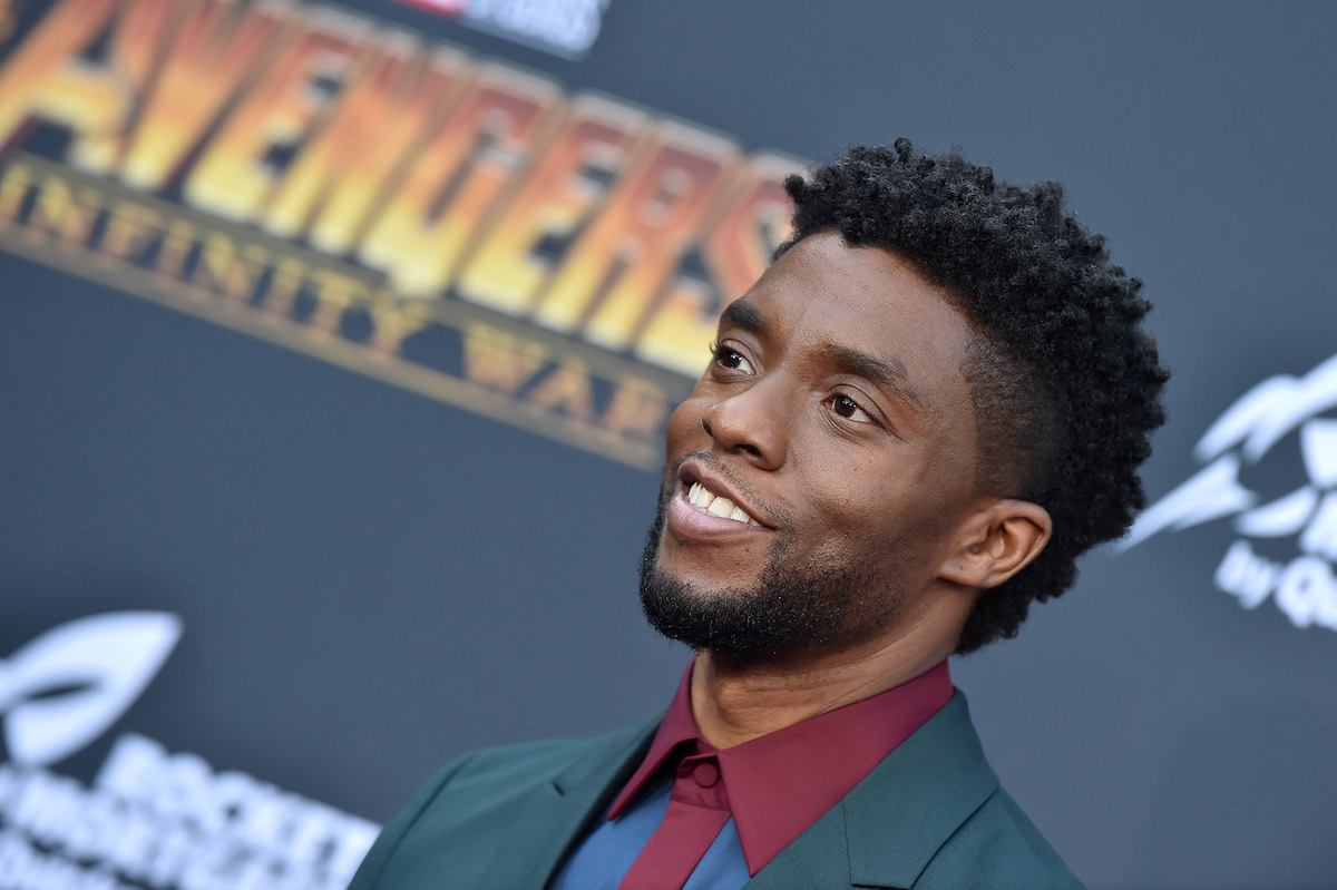 Chadwick Boseman smiles in a suit with a red shirt and black jacket at the 'Avengers: Infinity War' premiere