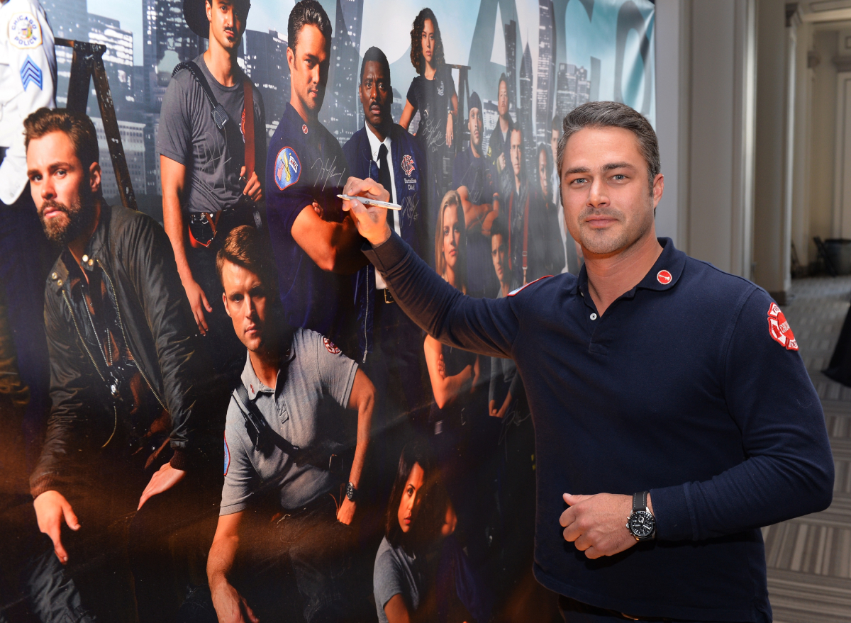 Taylor Kinney signs a poster as he attends a press junket for NBC's 'Chicago Fire', 'Chicago P.D.' and 'Chicago Med' at Cinespace Chicago Film Studios on November 9, 2015