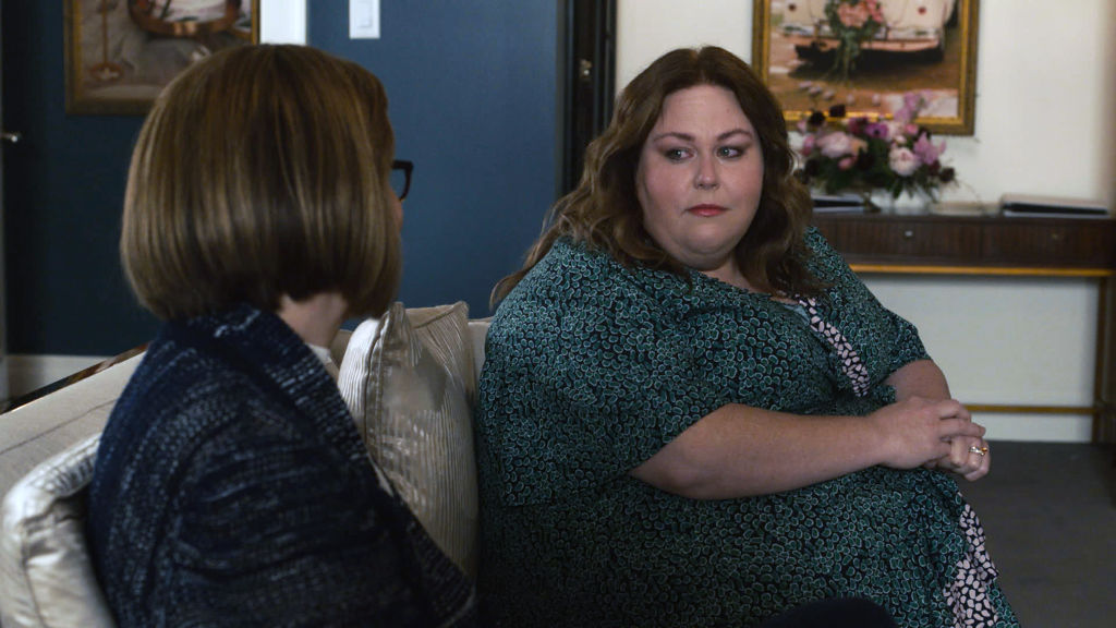 Mandy Moore as Rebecca, Chrissy Metz as Kate sit on a couch to talk. Kate is in a green dress and looks concerned.