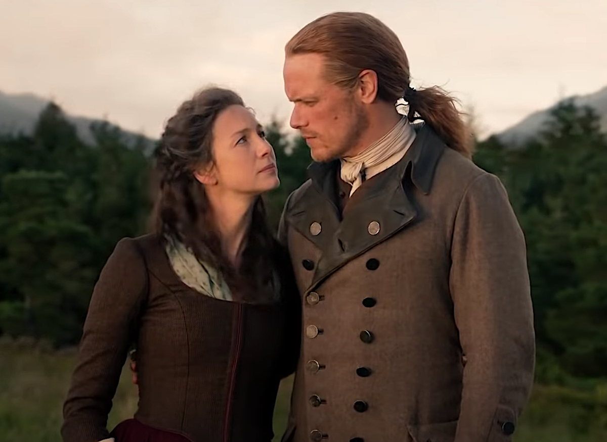 Caitriona Balfe wearing a brown long-sleeved dress as Claire and Sam Heughan in a brown coat with brass buttons and black lapels as Jamie in 'Outlander'