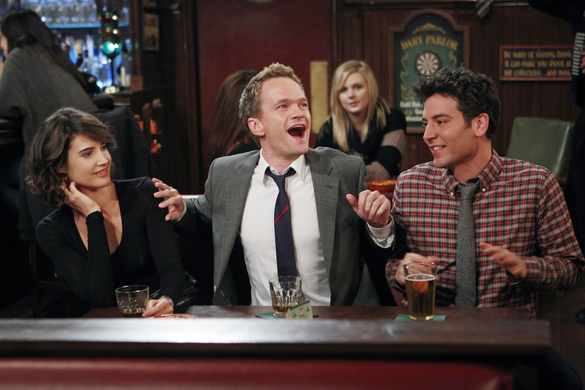 Neil Patrick Harris smiles and gestures wildly, while Cobie Smulders (left) and Josh Radnor (right) look on in a scene from 'How I Met Your Mother'