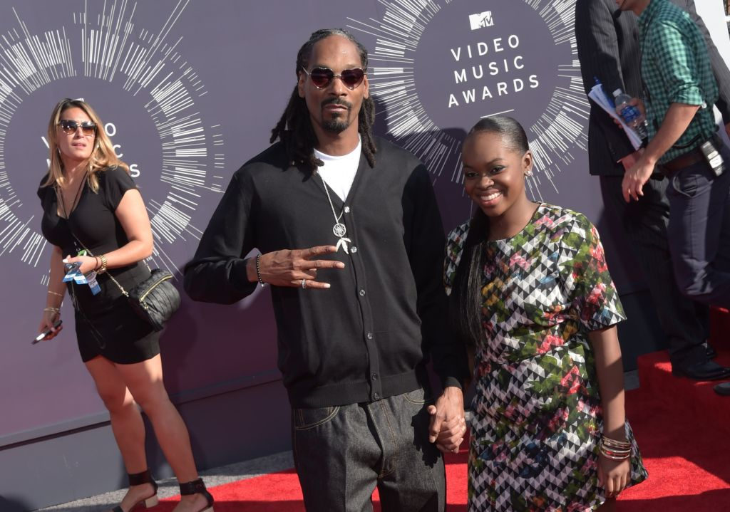 Rapper Snoop Dogg, dressed in a black zip-up, white t-shirt, and grey slacks, arrives with his arm around his daughter Cori Broadus, who's wearing a zig-zag, multi-colored dress on the red carpet for the 31st MTV Video Music Awards