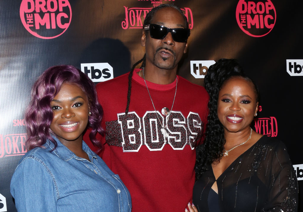 Cori Broadus, dressed in a blue denim shirt, stands with father Snoop Dogg who's wearing a red 'Boss' shirt, and her mother Shante Broadus who is wearing a lovely black dress, walk the red carpet with big smiles.