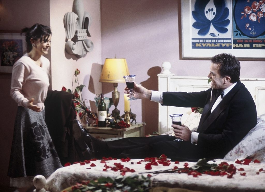 Courteney Cox Arquette as Monica Gelle walks into the room where Tom Selleck as Dr. Richard Burke sits on a bed of roses.