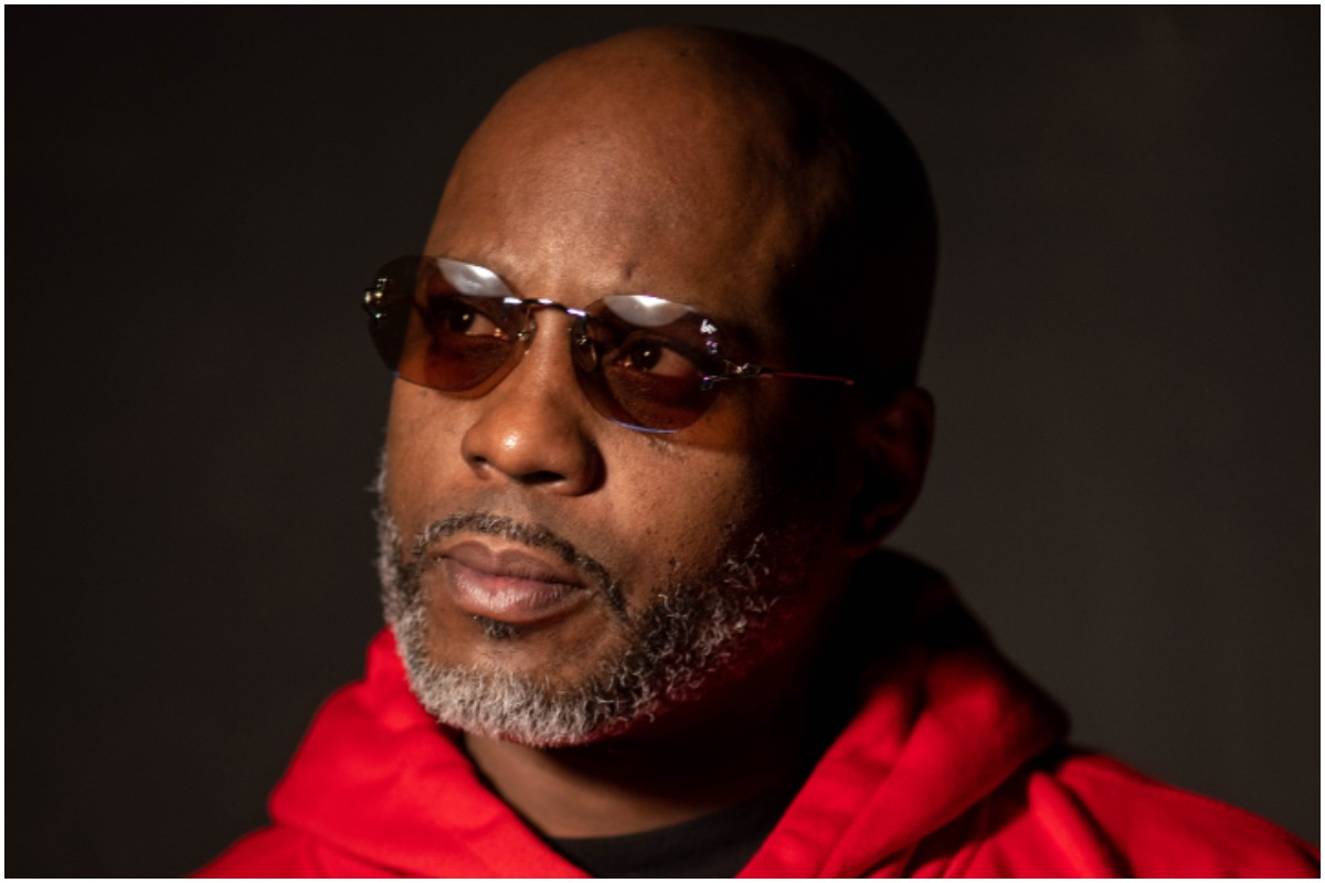 DMX looking away from the camera with black sunglasses and a red hoodie