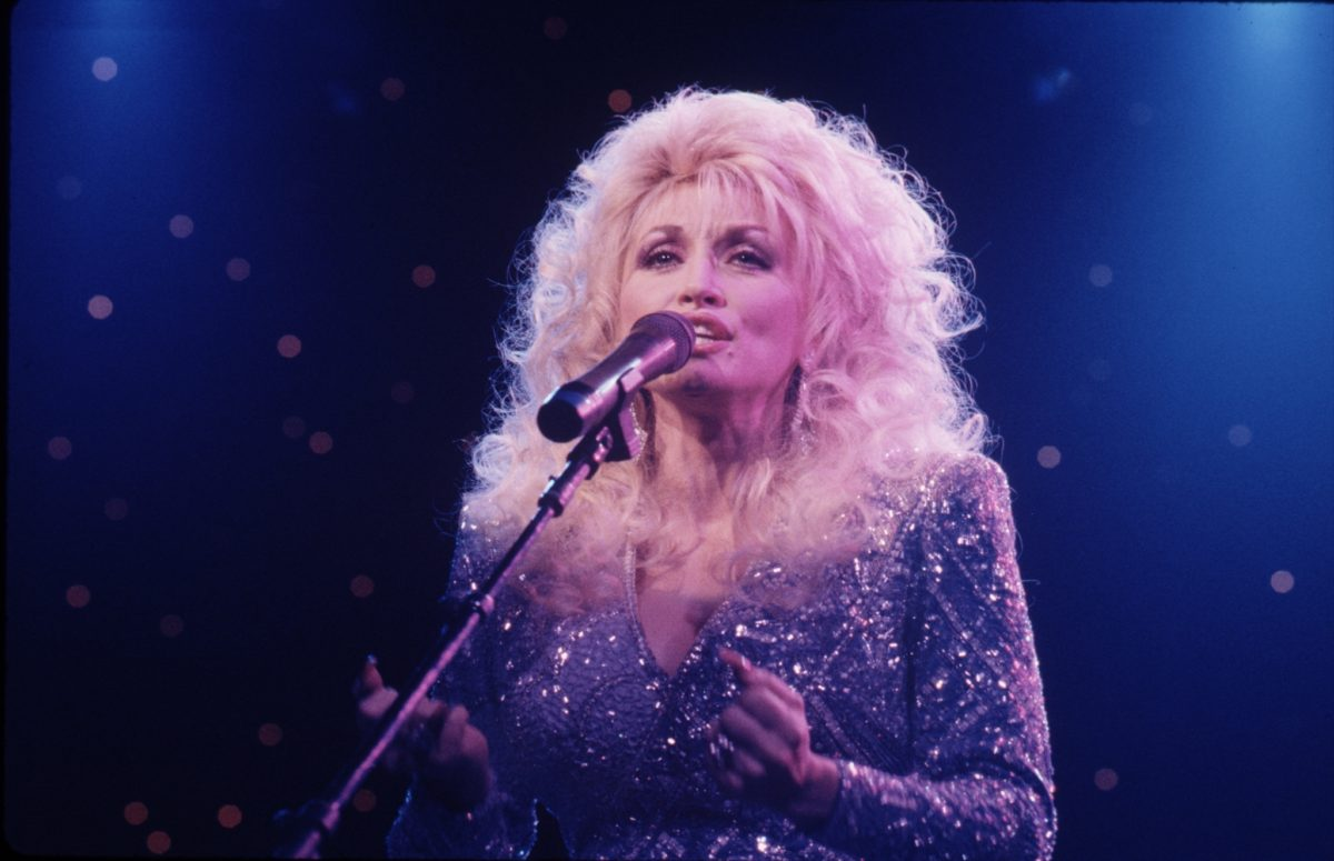 Dolly Parton singing into a microphone on stage.