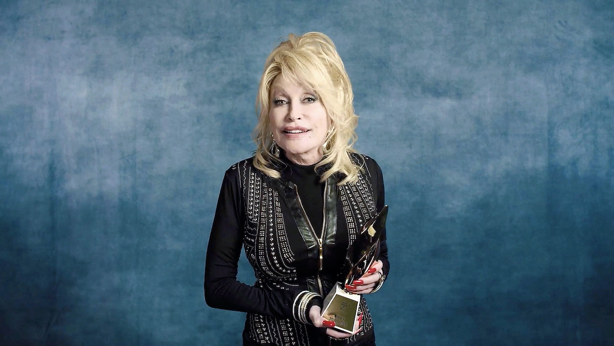 Dolly Parton smiles in a black outfit and a necklace at the We Are Family Foundation