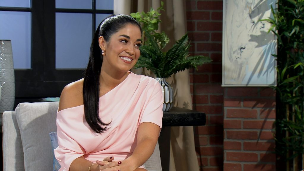 Dr. Viviana Coles has a ponytail and is wearing a pink dress sitting on 'Married at First Sight'