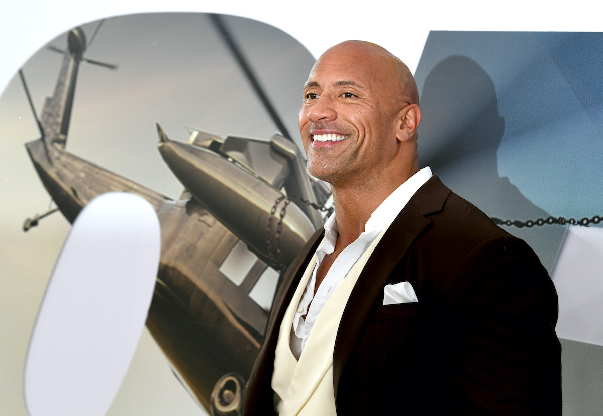 Dwayne Johnson poses in front of an image promoting 'Fast & Furious Presents: Hobbs & Shaw' at the movie's premiere