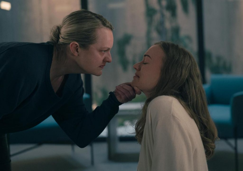 Elisabeth Moss as June looking angry and holding Yvonne Strahovski as Serena Joy Waterford's crying face in her hand in 'The Handmaid's Tale' Season 4. Moss wears a navy blue crew neck and Stahovski wears a cream colored blouse.