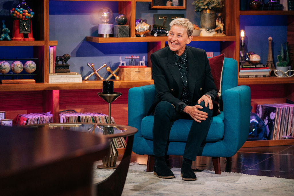 Ellen DeGeneres appears on 'The Late Late Show with James Corden' wearing a black suit as she sits in a chair, smiling.