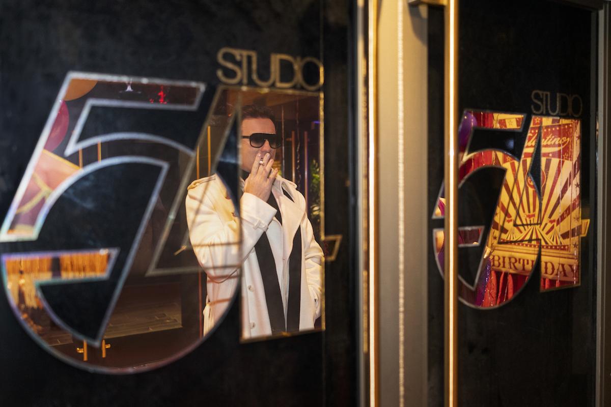 Ewan McGregor as Halston looking at windows of Studio 54