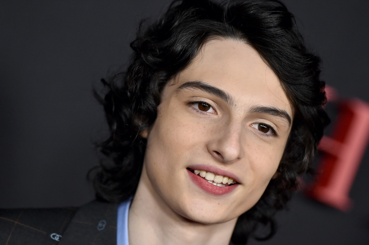 Finn Wolfhard in a blue shirt and black jacket at 'The Turning' premiere