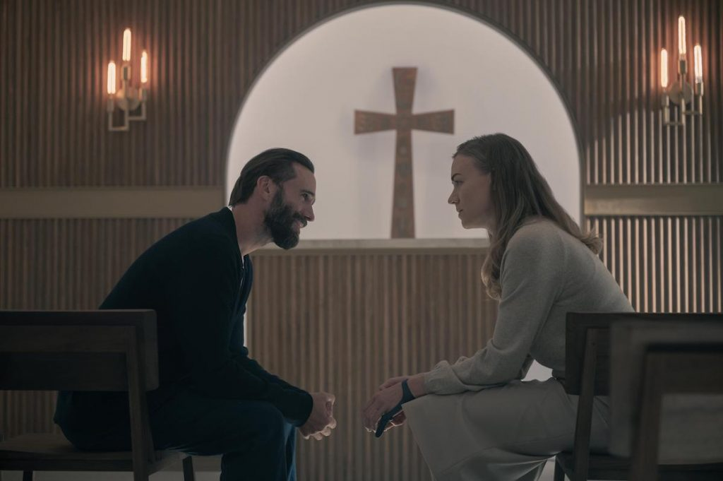 Joseph Fiennes (L) as Fred Waterford and Yvonne Strahovski (R) as Serena Joy Waterford sitting in a small chapel in 'The Handmaid's Tale' Season 4
