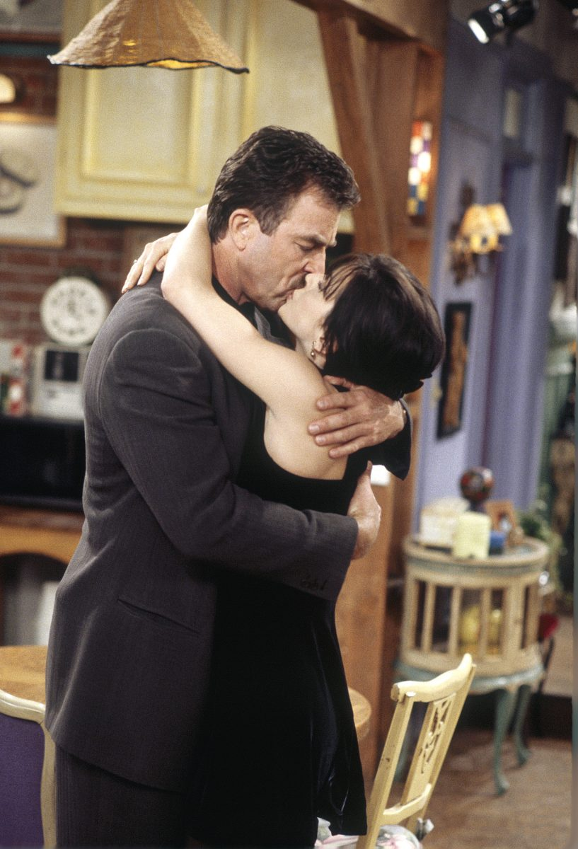 Tom Selleck as Richard Burke and Courtney Cox as Monica Geller kiss in Monica's apartment in season 2 of 'Friends'