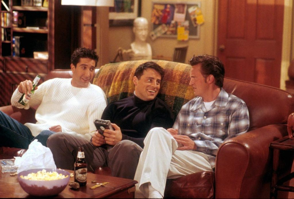 David Schwimmer, Matt LeBlanc, and Matthew Perry sitting on a couch in character on 'Friends'