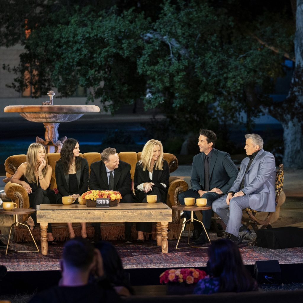 Friends: The Reunion cast sits on the couch in front of the fountain