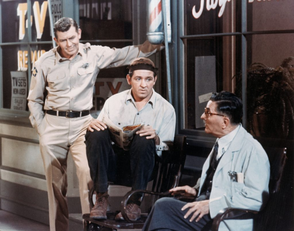 American actors Andy Griffith, George Lindsey, and Howard McNear sit outside Floyd's barber shop in a still from the television series, 'The Andy Griffith Show,' circa 1966.