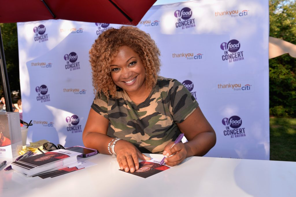 Food Network chef Sunny Anderson wears a camo top as she autographs photos at a Food Network concert, 2014