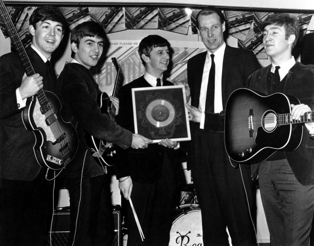 The Beatles pose with their record producer George Martin in 1964, left to right: Paul McCartney, George Harrison, Ringo Starr, Martin, and John Lennon