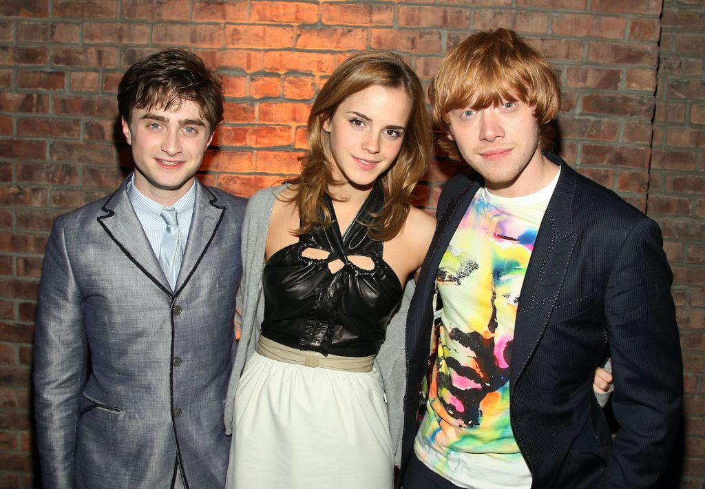 'Harry Potter' actors Daniel Radcliffe, Emma Watson, and Rupert Grint pose together in front of a brick wall