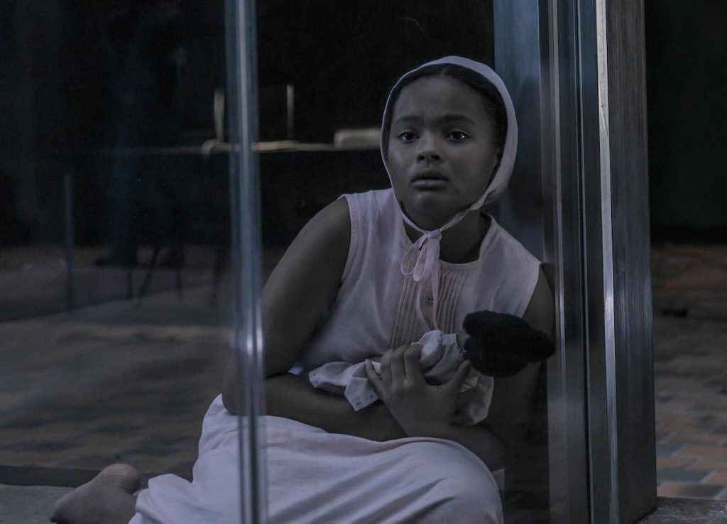 Jordana Blake in a pink dress and bonnet holding a doll while sitting in a glass room as Hannah in 'The Handmaid's Tale' Season 4