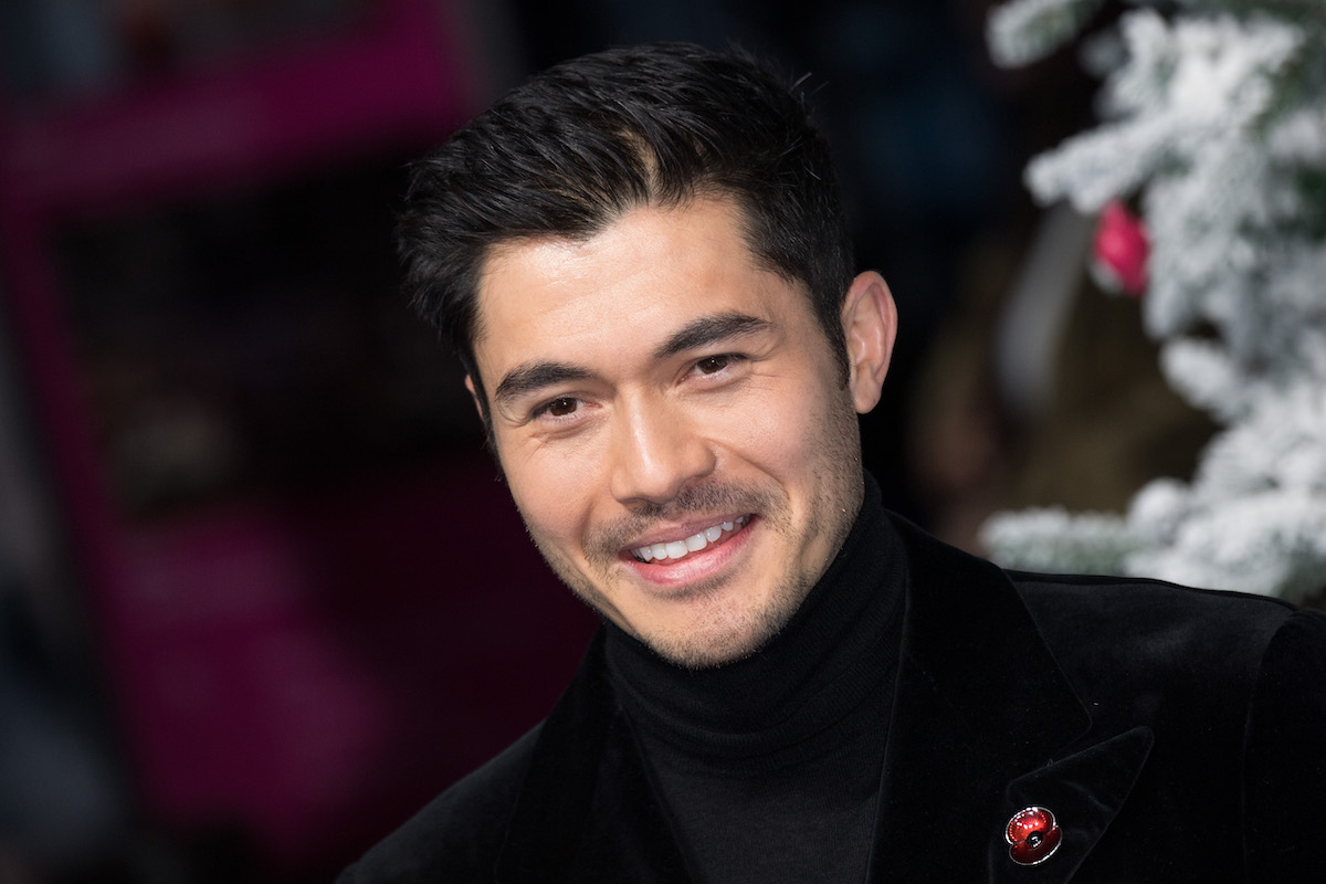 Henry Golding wears black and smiles at the UK premiere for 'Last Christmas'