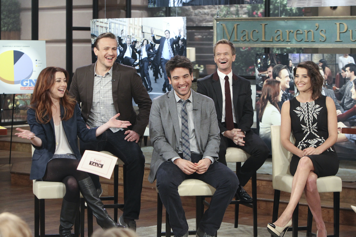 The cast of 'How I Met Your Mother' smile and laugh in front of images from the show on 'The Talk'