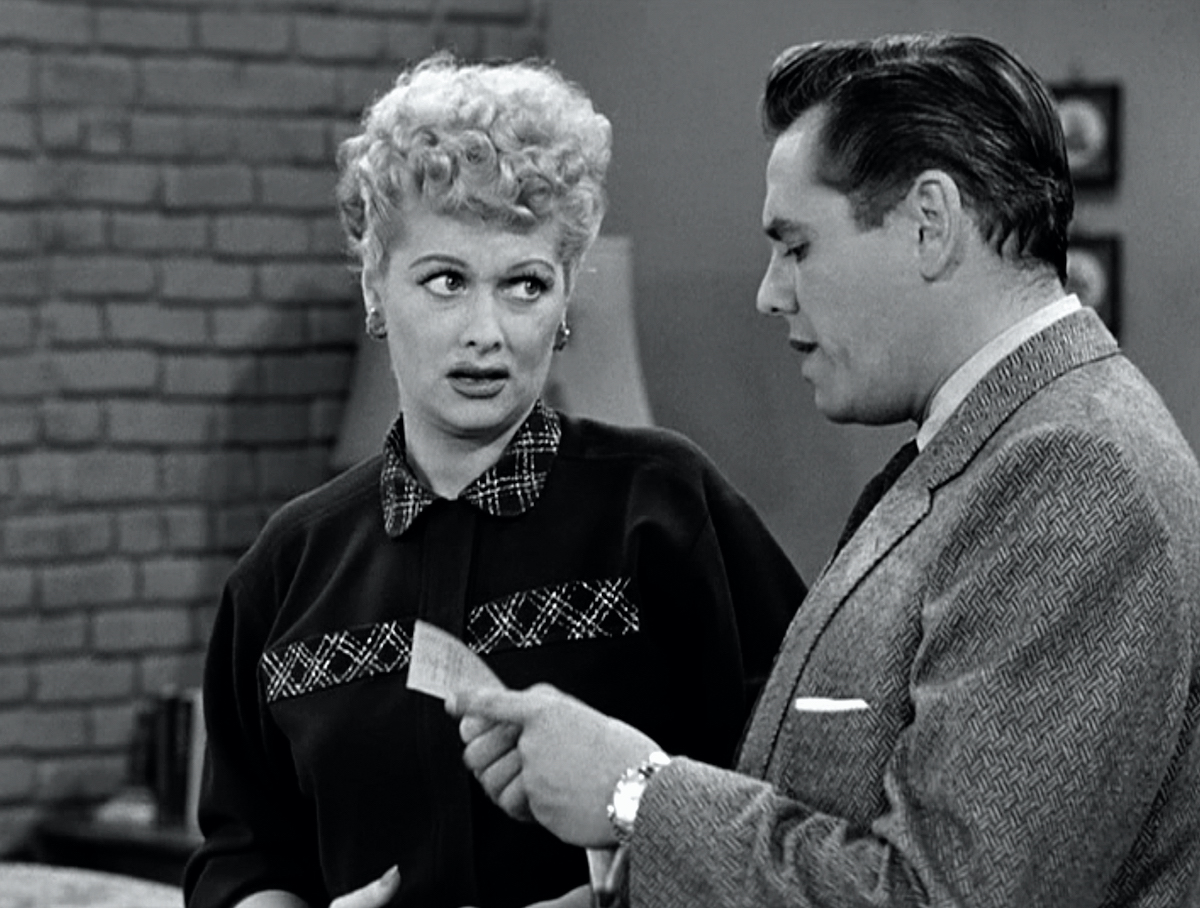Lucille Ball as Lucy Ricardo listens as Desi Arnaz as Ricky Ricardo pours a cup of coffee in the kitchen in 'I Love Lucy'