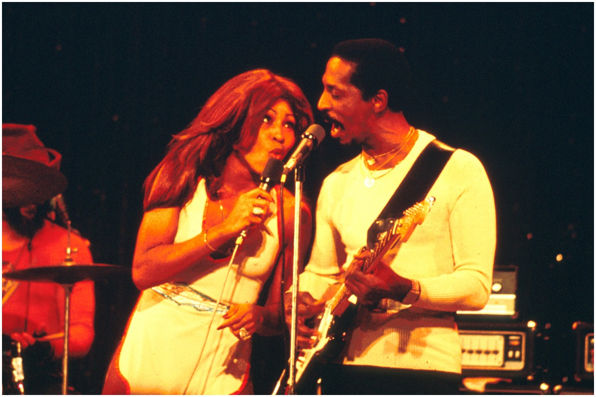 Tina Turner dancing and singing next to Ike Turner while wearing a white outfit. Ike is wearing a white shirt and black pants.