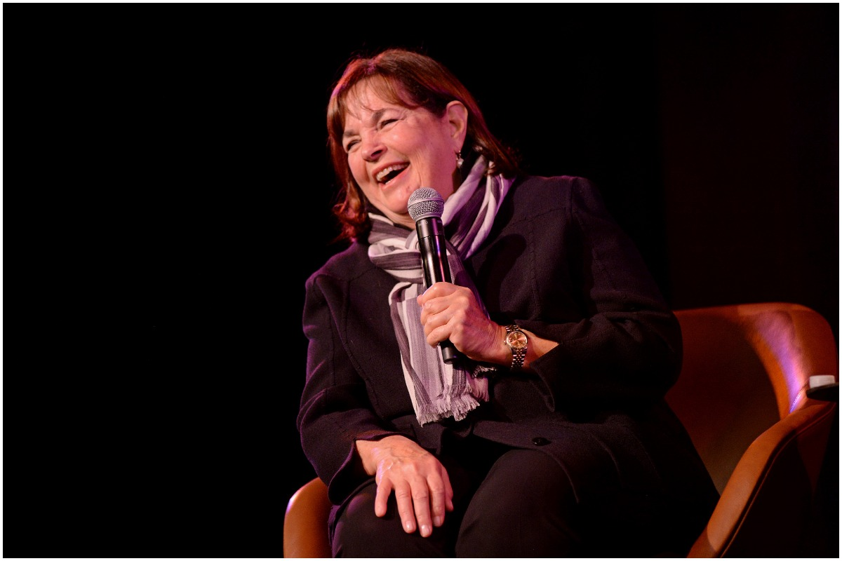 'Barefoot Contessa' star Ina Garten laughs while wearing an all-black outfit and a pattern scarf. She is holding a microphone onstage.
