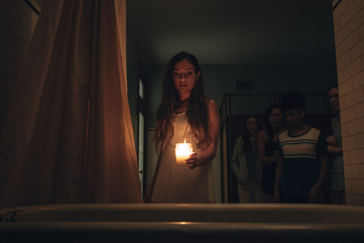 Inanna Sarkis holds a candle over a bathtub