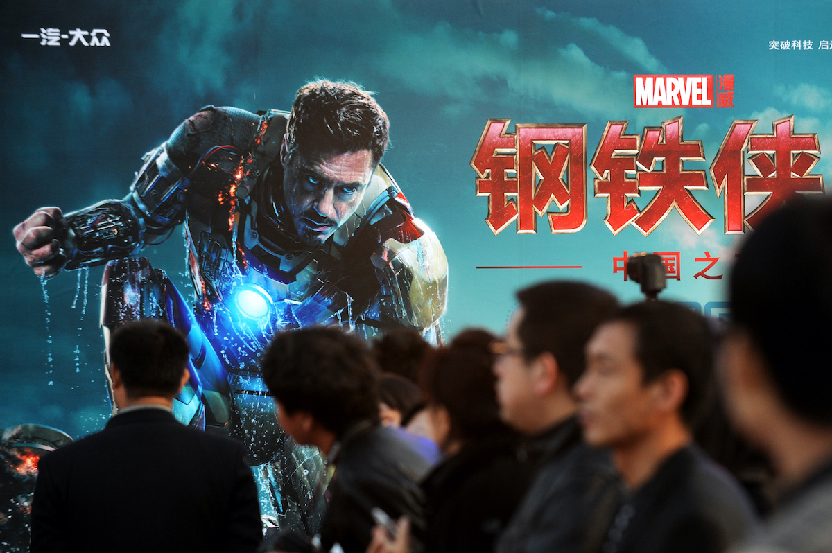 Attendees sit in front of a poster during a promotional event for 'Iron Man 3' in Beijing