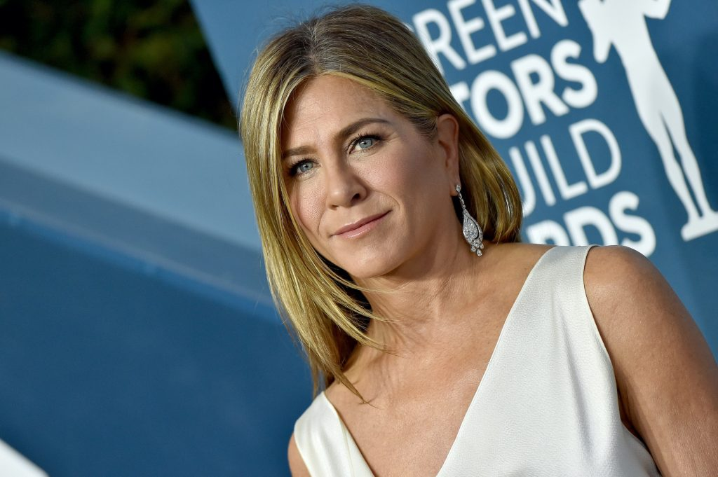 Jennifer Aniston smiling in front of a blue background
