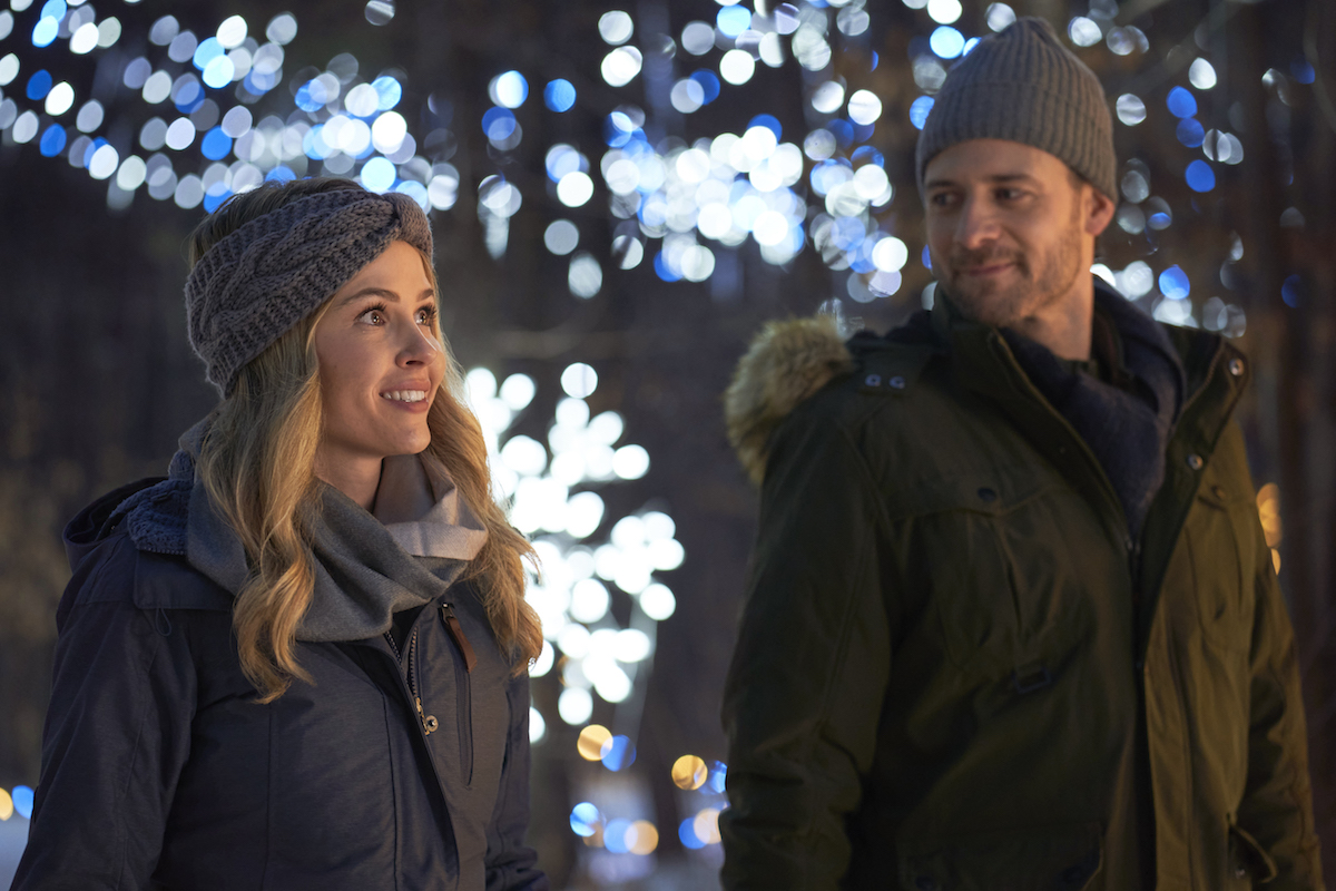 Jocelyn Hudon and Steve Lund, both wearing hats, in Hallmark movie Baby It's Cold Inside