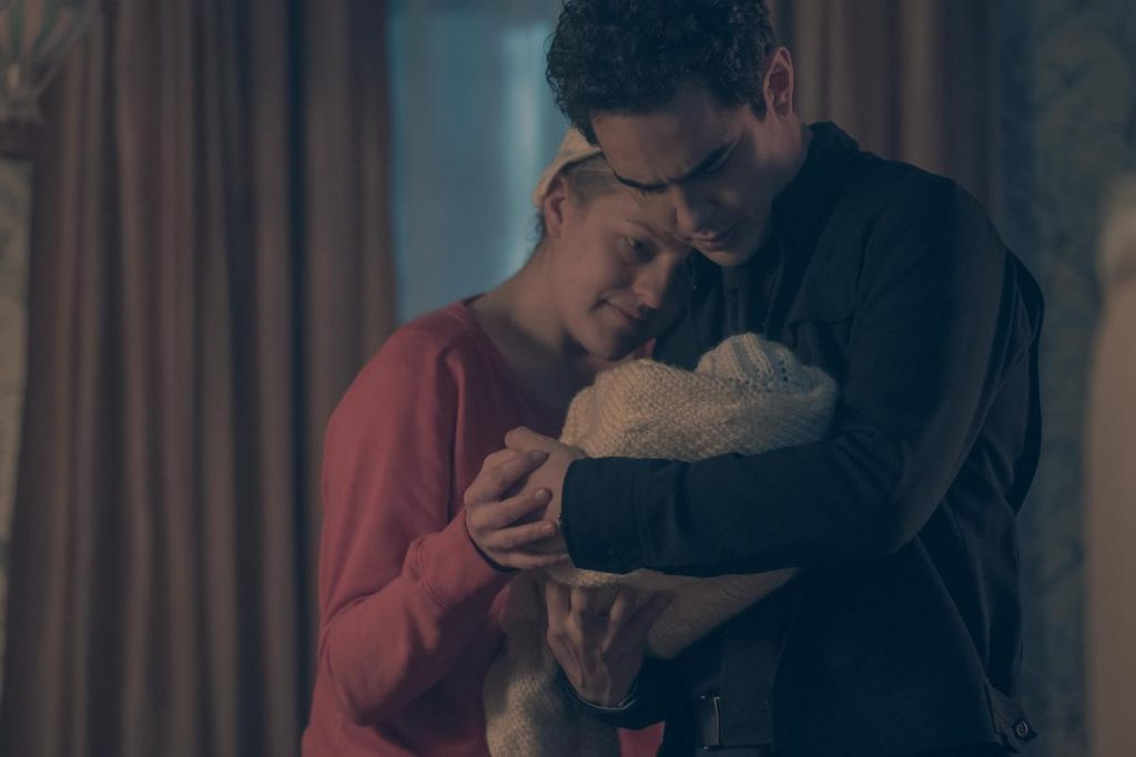 Elisabeth Moss in a red dress and white bonnet as June, Max Minghella in a black shirt and pants holding a baby wrapped in a white quilt in 'The Handmaid's Tale' Season 2