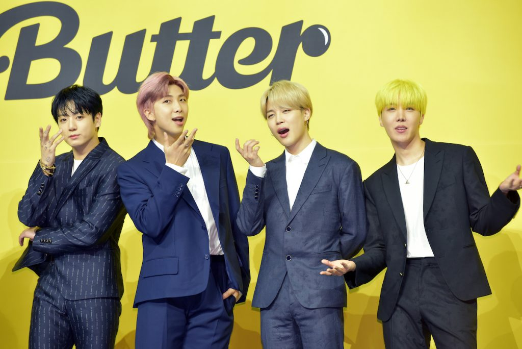 """Jungkook, RM, Jimin, and J-Hope of BTS pose in suits side by side in front of a yellow background that says """"Butter"""""""