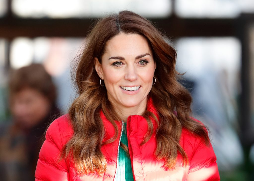 Kate Middleton smiling in a red coat