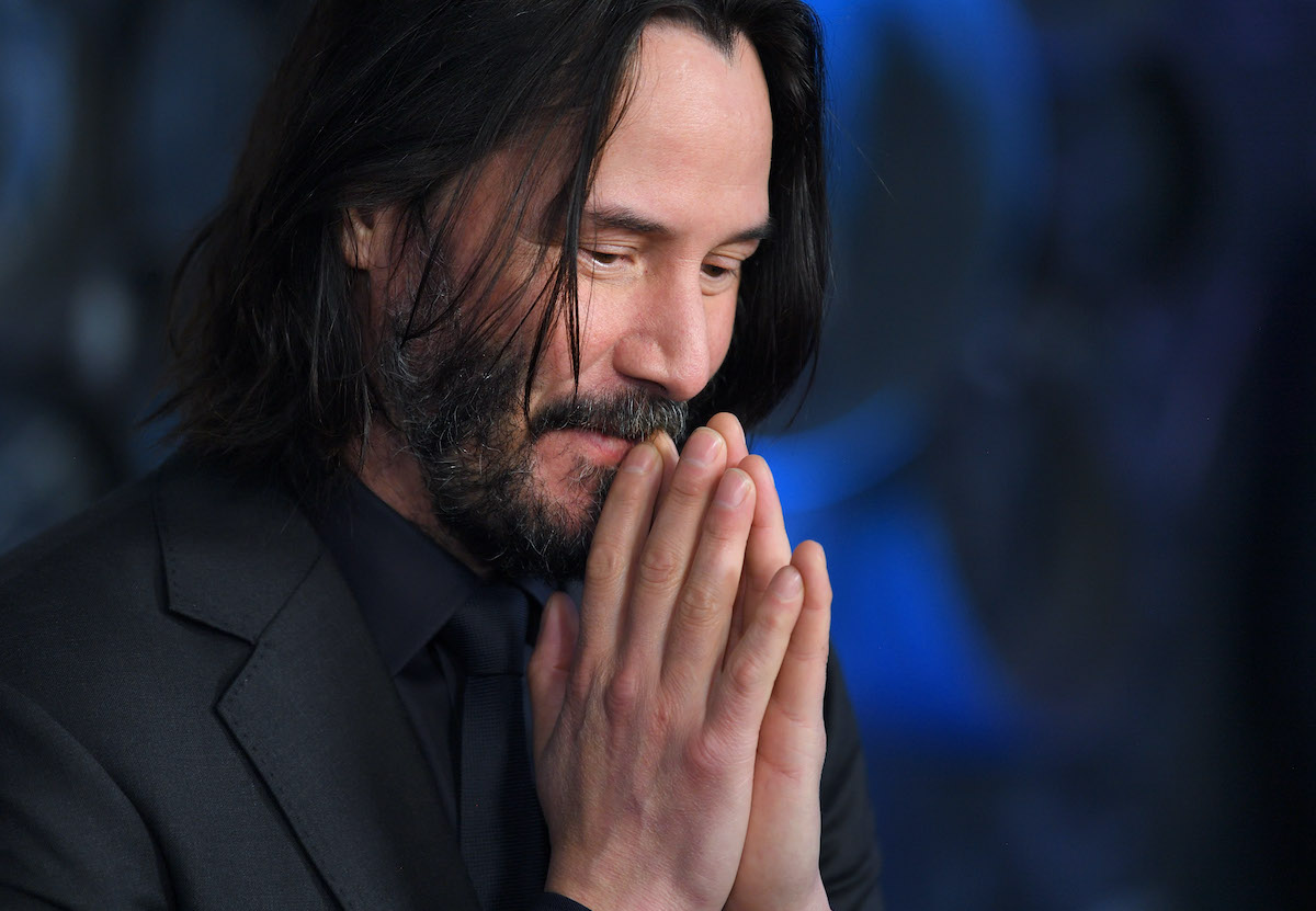 Keanu Reeves stands with his hands together at the 'John Wick: Chapter 3' special screening
