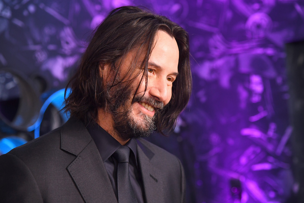 Keanu Reeves smiles in a black suit in front of a purple backdrop at 'John Wick' special screenings