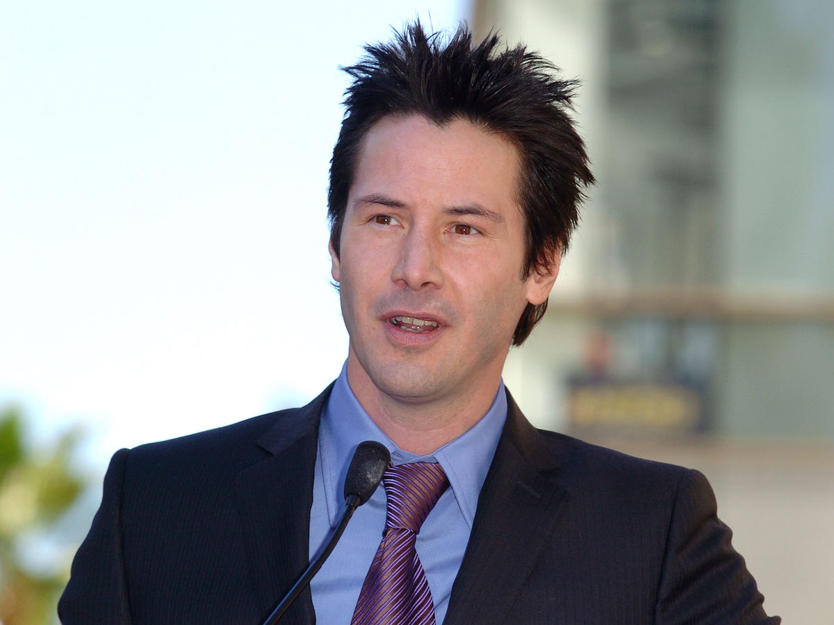 Keanu Reeves wears a suit and tie while speaking at a microphone