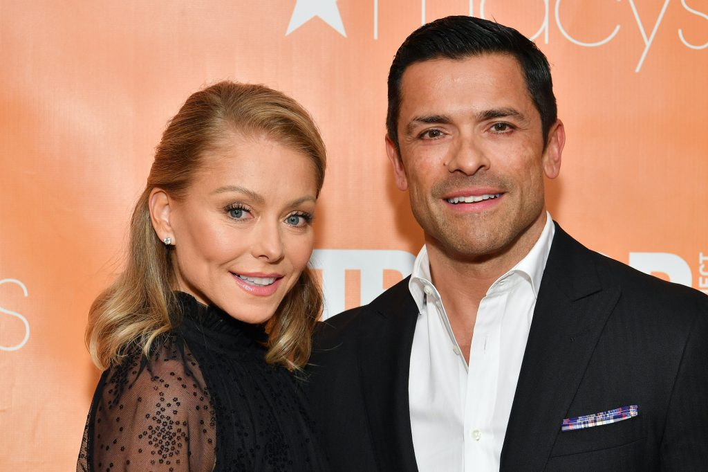 (L-R) Kelly Ripa and Mark Consuelos smiling in front of an orange background