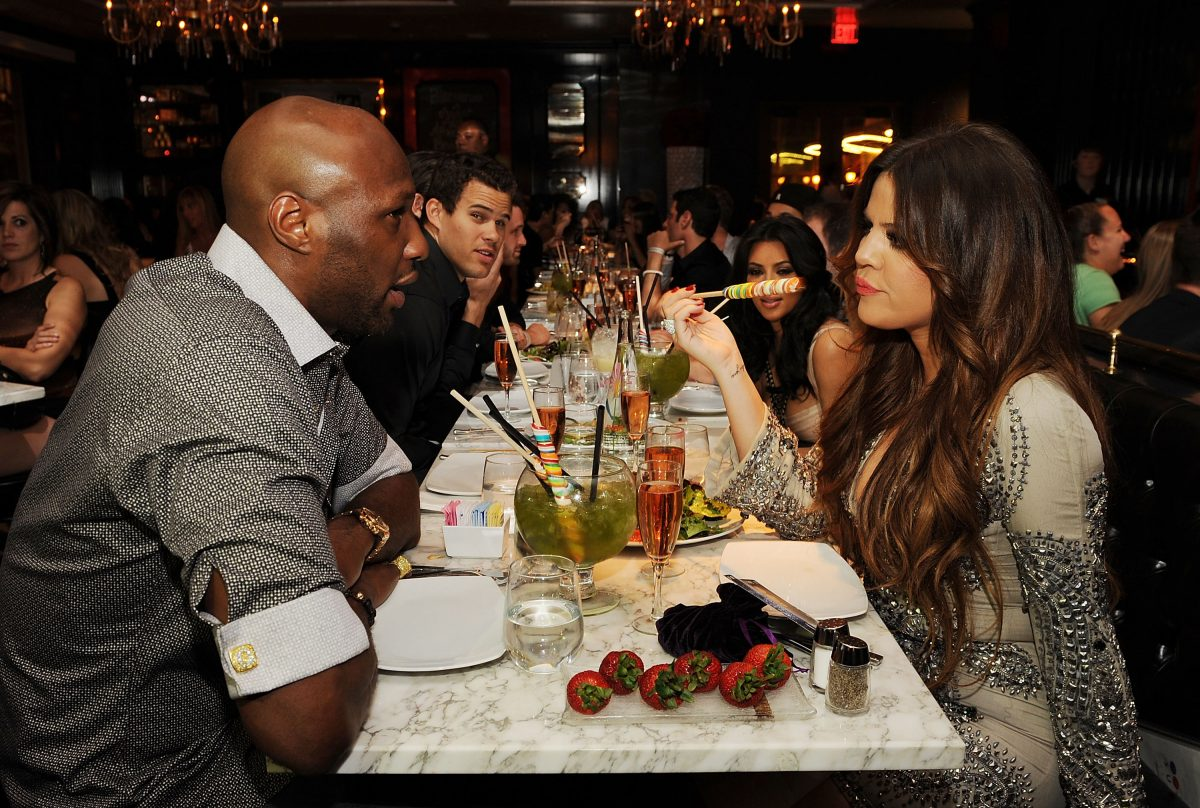 Khloé Kardashian and Lamar Odom staring at each other while having dinner with Kris Humphries and Kim Kardashian