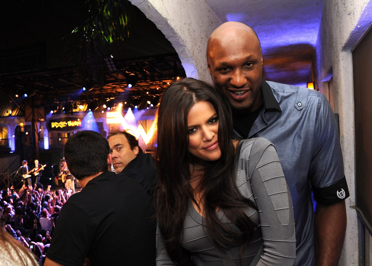 Khloé Kardashian wearing a grey dress while being embraced by Lamar Odom, who is wearing a dark blue shirt.