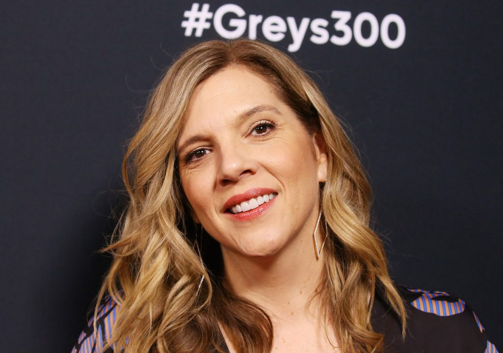 Krista Vernoff smiling in front of a #Greys300 sign
