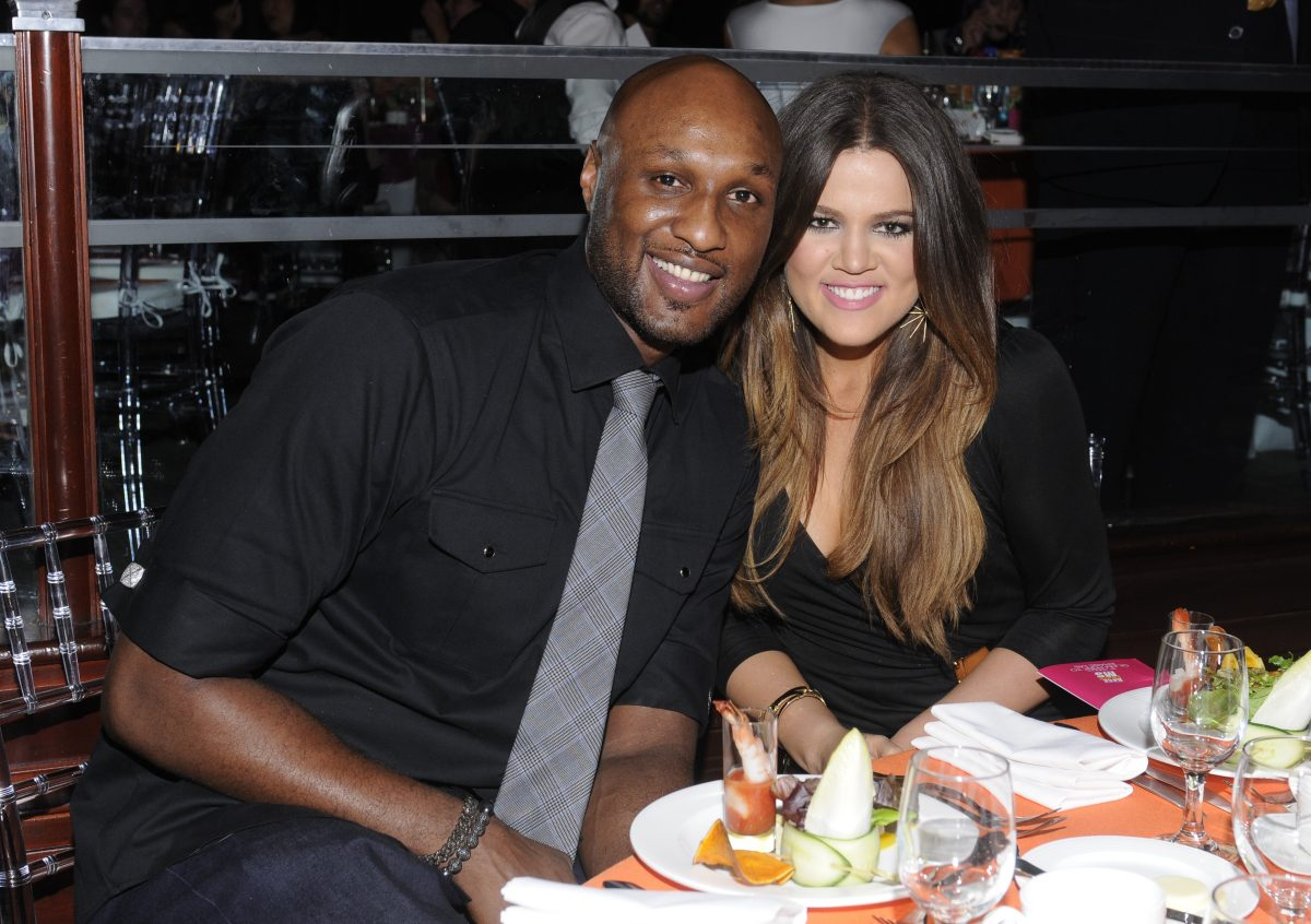 Lamar Odom in a black shirt and grey tie and Khloé Kardashian in a black dress smiling while having dinner.