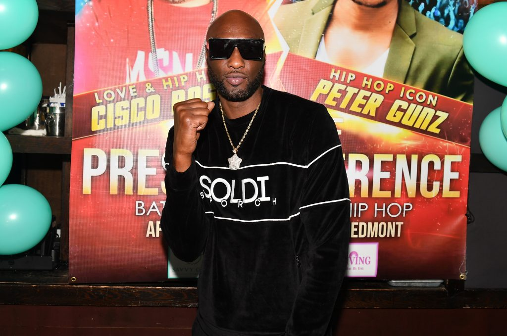 Lamar Odom dressed in a black sweater and making a fist at a celebrity boxing press conference