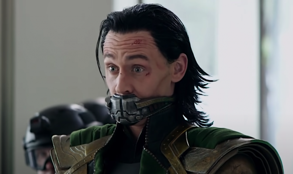 Tom Hiddleston with a metal mask over his mouth and his face cut up as Loki in 'Avengers: Endgame.'