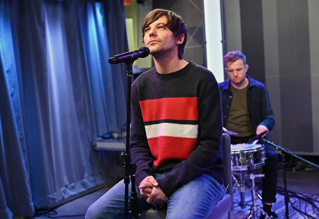 Louis Tomlinson performing in a sweater